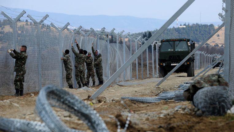 Macedonische soldaten versterken het hekwerk aan de grens met Griekenland. Beeld EPA