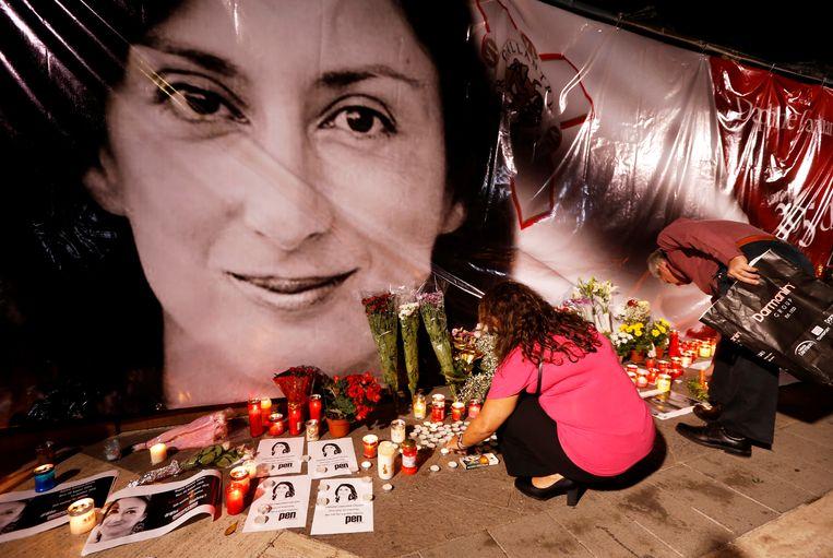 Mensen leggen bloemen en kaarsen bij een herdenking van de dood van journaliste Daphne Caruana Galizia. Beeld REUTERS