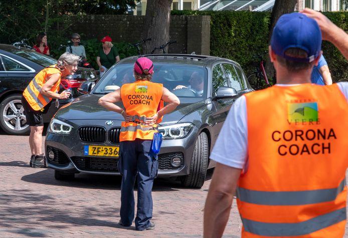 Corona coaches leiden het verkeer in Domburg in goede banen en wijzen mensen op de afspraken: geen auto's en fietsen in de winkelstraat en anderhalve meter afstand houden. Marja Wedts de Swart (links) geeft informatie aan een automobilist.