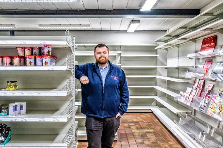 Directeur Ryan Pierce tussen de lege schappen van Stonemanor in Everberg, een supermarkt gespecialiseerd in Britse producten.   Beeld Tim Dirven