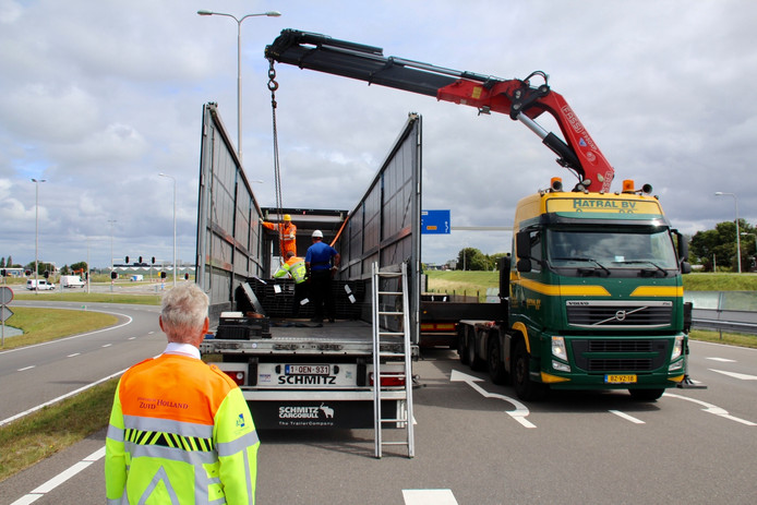 Een bergingsbedrijf en kraanbedrijf takelen samen de lading uit de vrachtwagen
