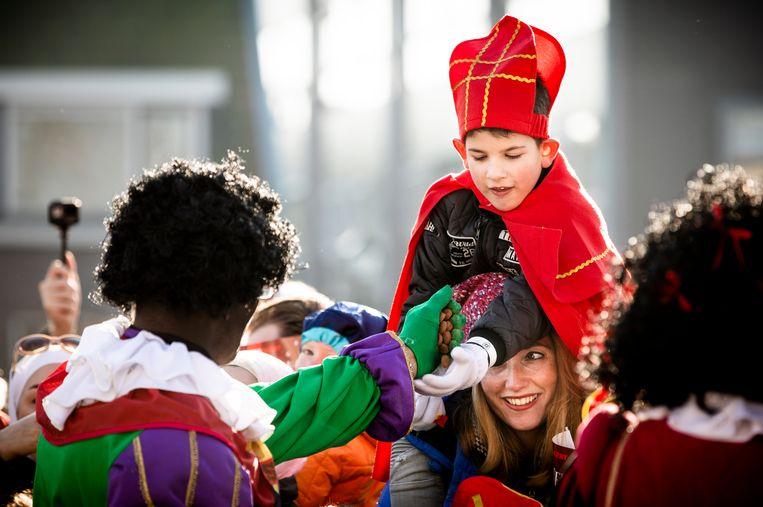 ZAANSTAD - Zwarte Piet deelt pepernoten uit aan het publiek langs de route tijdens de landelijke intocht van Sinterklaas op de Zaanse Schans. De oer-Hollandse Zaanse Schans is dit jaar het decor van de landelijke intocht van de goedheiligman en zijn pieten. ANP FREEK VAN DEN BERGH Beeld Hollandse Hoogte /  ANP