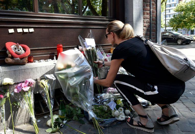 Passanten herdenken de slachtoffers met bloemen.  Beeld Photo News