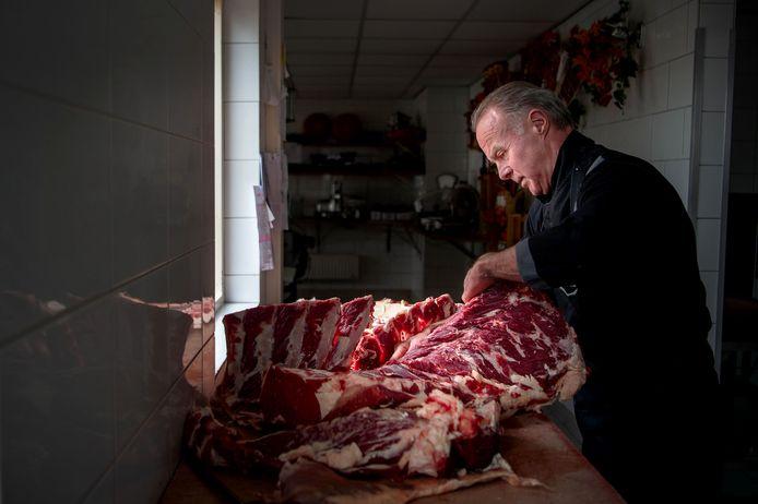 Slager Arjan Hendriks bezig met het uitsnijden van een runderlende. ,,Alle runderen en varkens komen uit Maas en Waal.''
