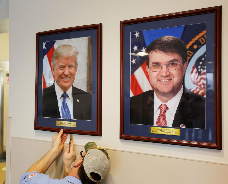 Het portret van Trump wordt verwijderd Beeld Photo News