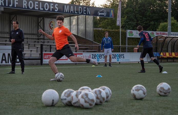 Twan Smits haalt uit onder toeziend oog van Juliana'31-coach Remko Bicentini (links), bij een (corona)training eerder dit jaar.