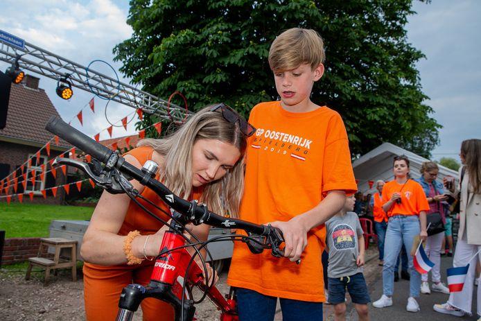 Merel Smulders signeert de mountainbike van een jonge fan tijdens de huldiging in haar dorp Horssen.