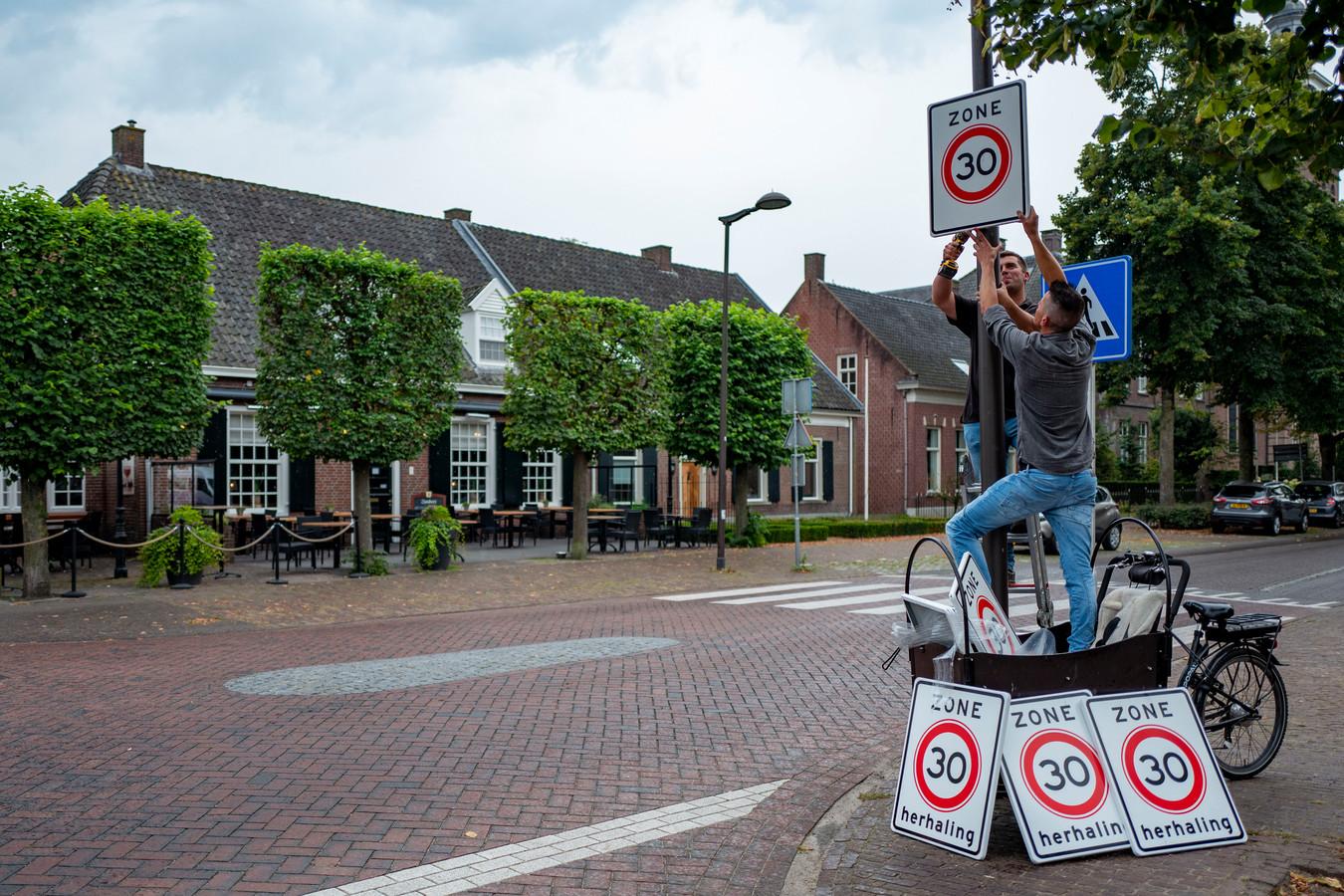 Dirk van de Ven (rechts) en op de trap Bart Vervoort hangen de verkeersborden op.