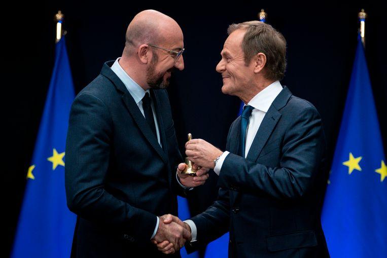 Donald Tusk overhandigt zijn opvolger Charles Michel het ceremoniële voorzittersbelletje.  Beeld AFP