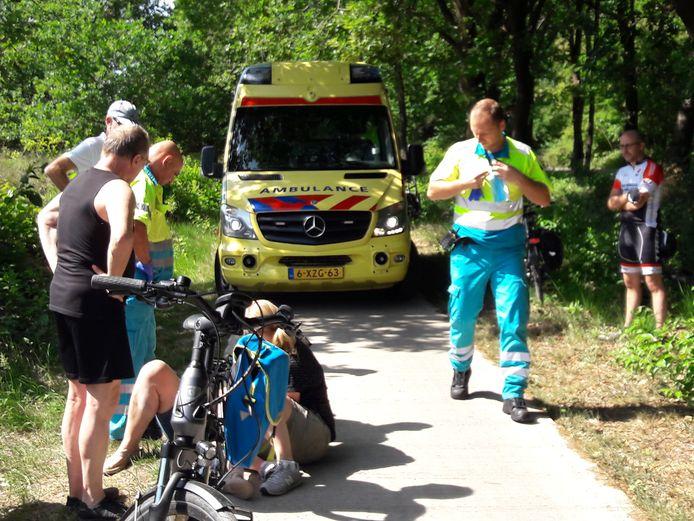 De fietsster wordt nagekeken door ambulancepersoneel.