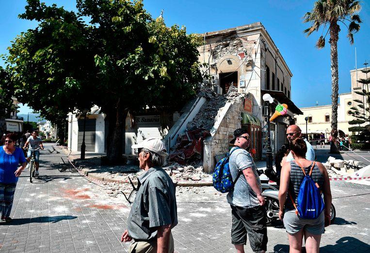 ► Toeristen staan wat verdwaasd naast gebouwen op Kos die beschadigd werden door de aardbeving. Beeld AFP