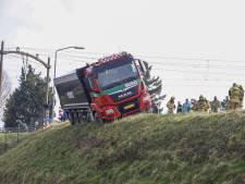 Vrachtwagen belandt in berm en balanceert op dijk