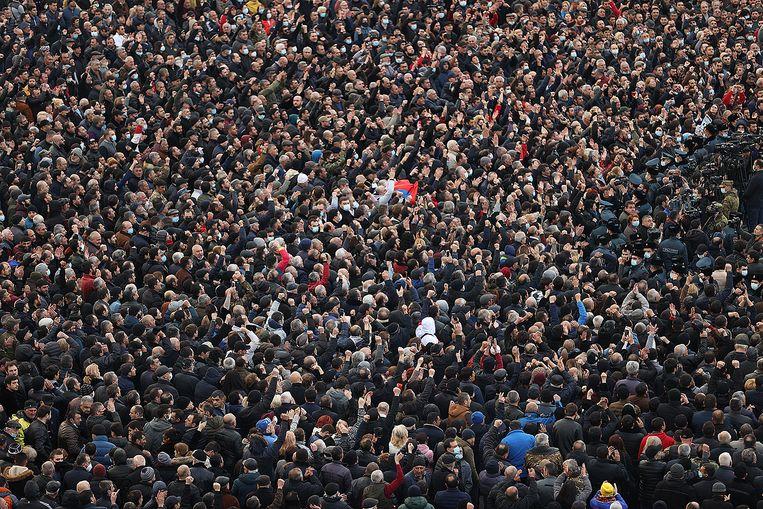 Aanhangers van de Armeense president Nikol Pasjinjan trekken door de straten van Jerevan. Beeld AFP