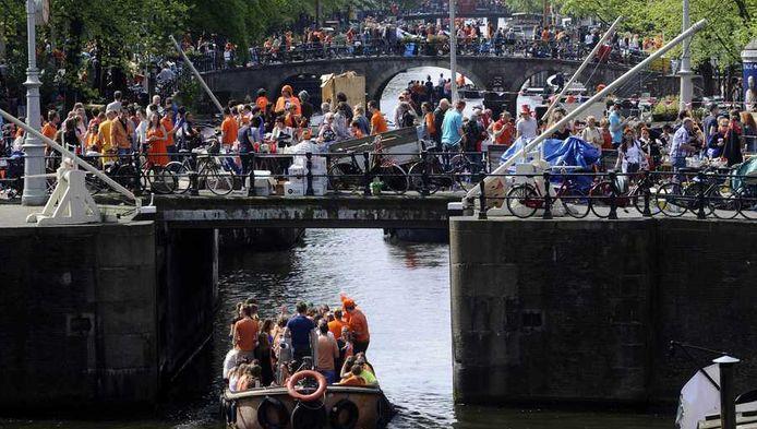 In Amsterdam is het druk tijdens Koningsdag. Bezoekers zijn oranje uitgedost en bootjes vol feestvierders gaan de grachten op