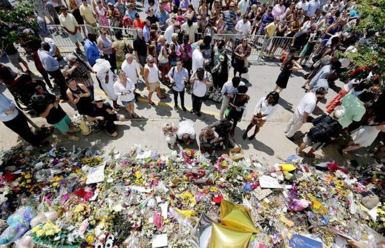 Mensen leggen bloemen en andere steunbetuigingen voor de Emanuel A.M.E.-kerk in Charleston, South Carolina. Beeld EPA