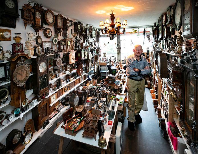 Gerrit Pennings tussen een deel van zijn grote verzameling uurwerken.