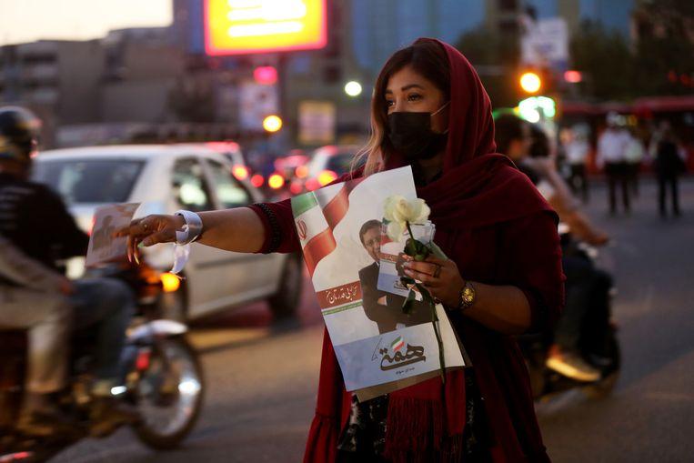 Een aanhanger van de hervormingsgezinde Abdolnaser Hemmati deelt folders en bloemen uit in Teheran, 16 juni. Beeld Fatemeh Bahrami / Anadolu / Getty