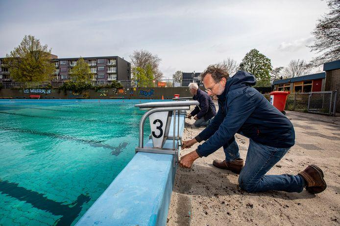 Jack Albas (op de voorgrond) en Jaap van Adrichem bezig met de laatste loodjes voordat zwembad De Waterman in Wateringen bij hogere temperaturen weer open kan.