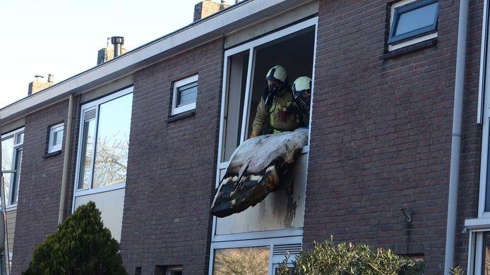 De brandweerlieden gooien het verbrande matras naar buiten.