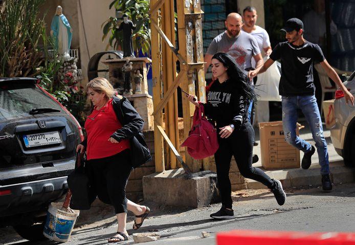 Des chrétiens libanais fuient leurs maisons sous les tirs de snipers après que des affrontements meurtriers aient éclaté le long d'une ancienne ligne de front de la guerre civile de 1975-90 entre les zones musulmanes chiites et chrétiennes, dans le quartier d'Ain el-Remaneh, à Beyrouth, au Liban, ce jeudi 14 octobre 2021.