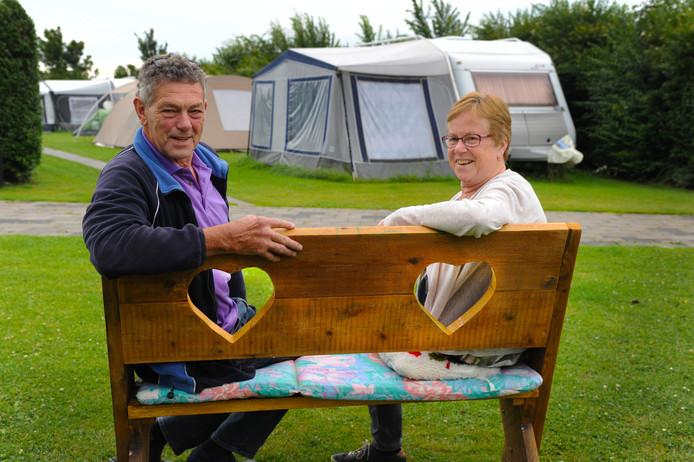 Han en Marleen Kole op een bankje op hun minicamping in Biggekerke.