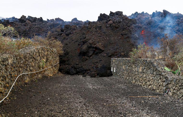 Een lavastroom kruist een oprit van een huis op La Palma. Beeld Reuters