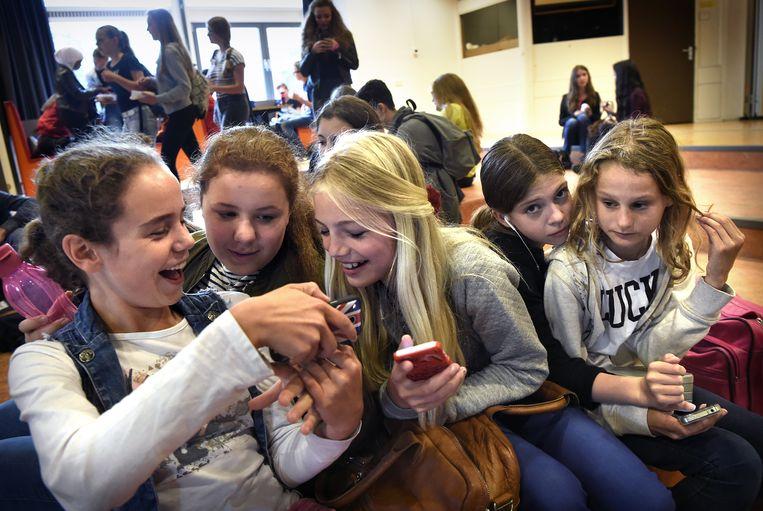 Leerlingen van een middelbare school in Nijmegen met hun mobieltjes.   Beeld Marcel van den Bergh/de Volkskrant