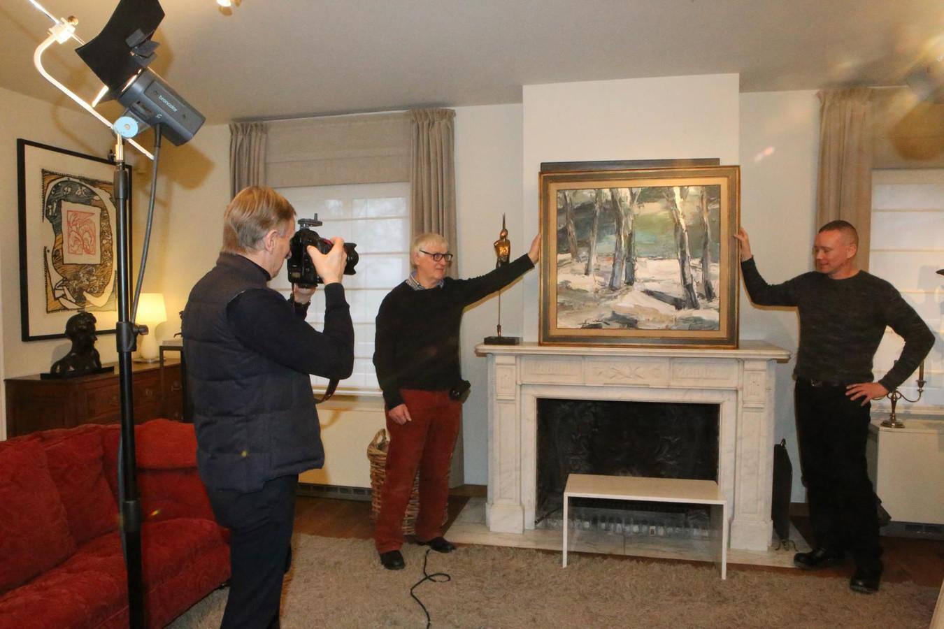 Kunstliefhebber François Renier en initiatiefnemer Pieter Van Kerckhof houden een schilderij van Emile Deca vast, terwijl André Matthijssens het werk fotografeert.