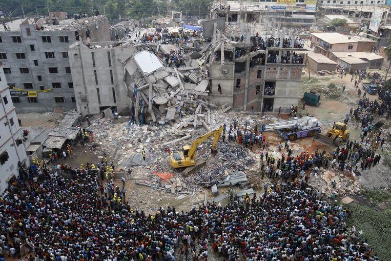 Op 25 april 2013 stortte de fabriek Rana Plaza in Bangladesh in. Omstanders kijken toe terwijl er naar overlevenden gezocht wordt. Beeld epa
