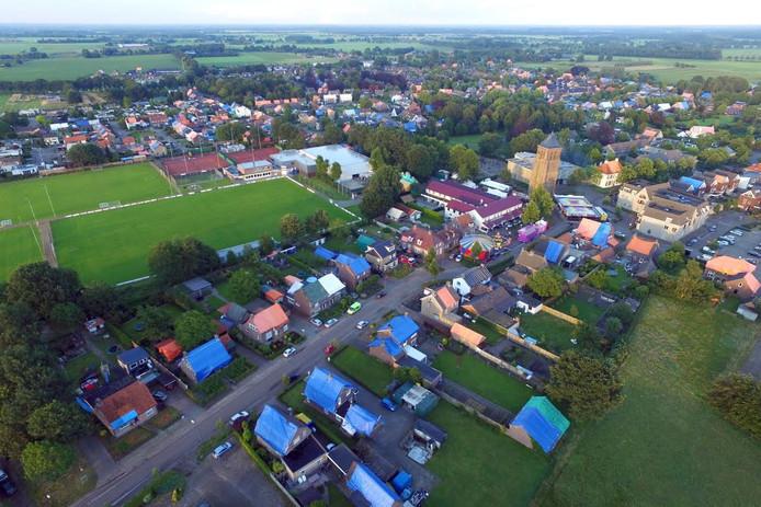 Een luchtfoto van Luyksgestel die zondag werd gemaakt, laat zien hoe groot de schade na de hagelstorm van donderdagavond is. Vrijwel alle daken zitten vol gaten en zijn daarom afgedekt met blauwe en oranje zeilen.