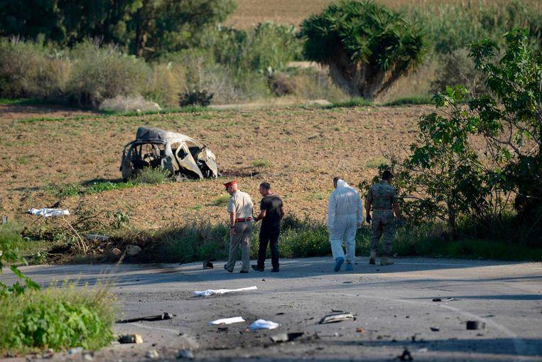 Politieonderzoek op de plek waar de ontploffing plaatsvond. Op de achtergrond het wrak, waar Galizia zich op het moment van de ontploffing bevond Beeld ANP