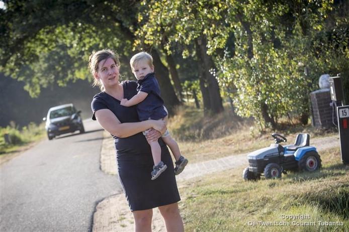 Wies Vluttert, op de foto samen met haar zoontje Guus, heeft een speelgoed tractor langs de weg (Oude Postweg) gezet tegen hardrijders.