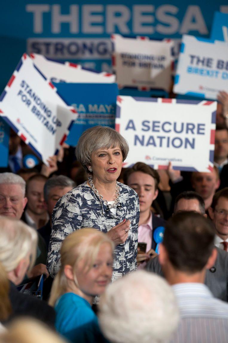 De Britse premier Theresa May spreekt haar supporters toe tijdens een campagne van de Conservatieven. Als we de peilingen mogen geloven, behoudt ze haar ambt. Beeld EPA