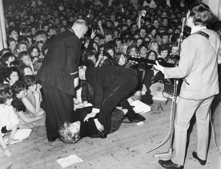 Een fan valt flauw voor John Lennon's voeten. Beeld  Bettmann/CORBIS