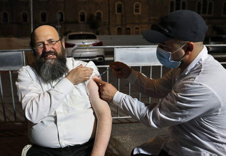 Een oudere Israëli krijgt zijn derde dosis van het Pfizervaccin. Beeld AFP