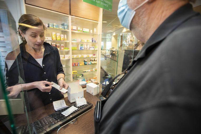 Een klant koopt een zelftest bij een apotheek.  Beeld ANP