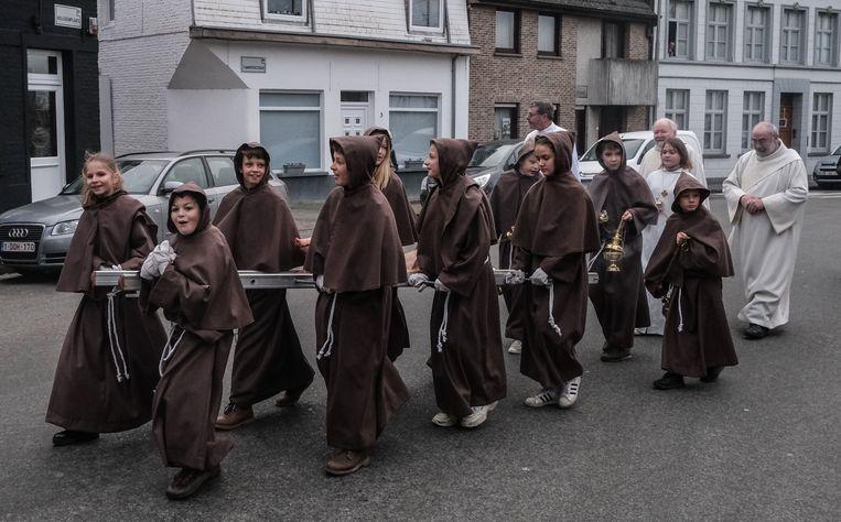 De jonge vormelingen op weg met het varken naar de kerk.