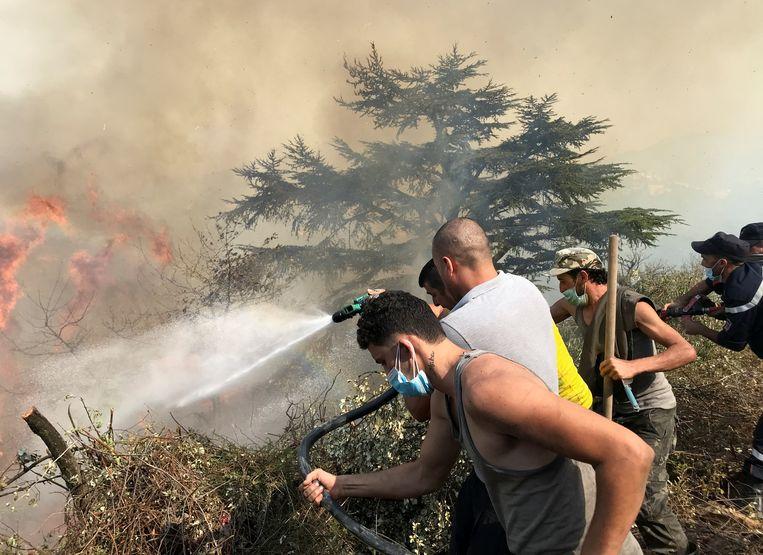 Vrijwilligers gaan het vuur te lijf met een tuinslang in Tizi Ouzou in Algerije. Beeld REUTERS