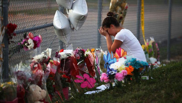 Een student van de Marjory Stoneman Douglas High School legt bloemen neer na de schietpartij op haar school. Beeld null