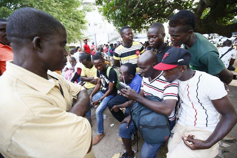 Aanhangers van de CPC beluisteren de verkiezingsuitslag in Liberië. Beeld EPA