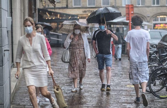 Regen verrast terrasbezoekers op de Grote Markt in Ieper.