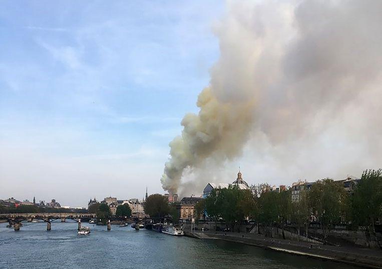 Er stijgt rook op vanuit de Notre-Dame op het Île de la Cité in Parijs. Beeld AFP