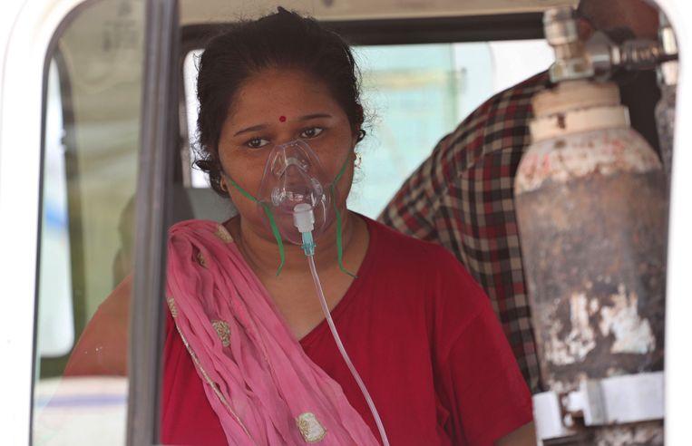 Een coronapatiënt wacht om te worden opgenomen in een speciaal coronaziekenhuis in de Indiaase stad Ahmedabad. Het Zuid-Aziatische land meldde donderdag een wereldwijd record van meer dan 314 duizend nieuwe infecties in een etmaal. Beeld AP