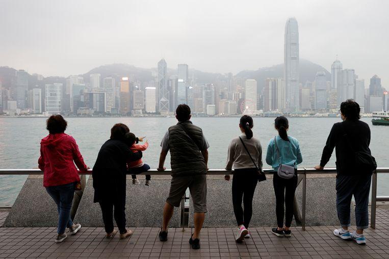 De familie Lai, die binnenkort naar Schotland emigreert, kijkt nog een keer naar de skyline van Hongkong. Beeld Reuters