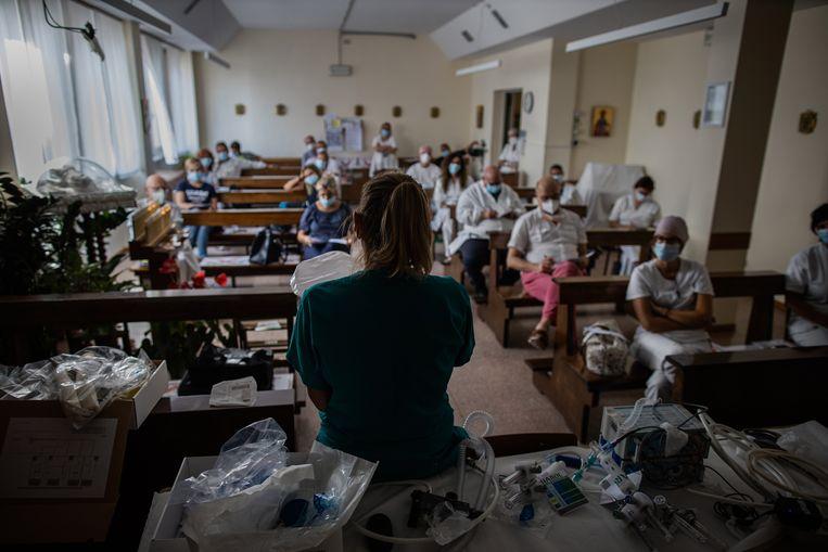 Dokter Monica Avogadri legt in de kapel van het Pesenti Fenaroli-ziekenhuis aan verzorgend personeel uit hoe de beademingstoestellen werken. Beeld NYT/FABIO BUCCIARELLI