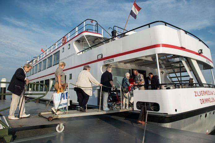 Vrijwilliger Jo de Bruijn (tweede van rechts, geruit overhemd) helpt de mensen mee aan boord.