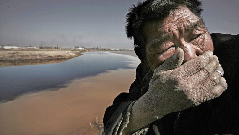 Om stil van te worden... Deze Mongoolse herder moet zijn adem inhouden door de stank van de vervuilde Yellow River.