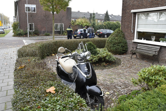 Terwijl agenten de gegevens van betrokkenen noteren, staat de betrokken scooter in een tuin geparkeerd.