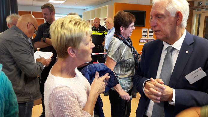Wethouder Frans Stienen (rechts) luistert naar bezorgde buurtbewoonster Karin Deelen tijdens de inloopavond over de huisvesting van arbeidsmigranten in Rijpelberg.