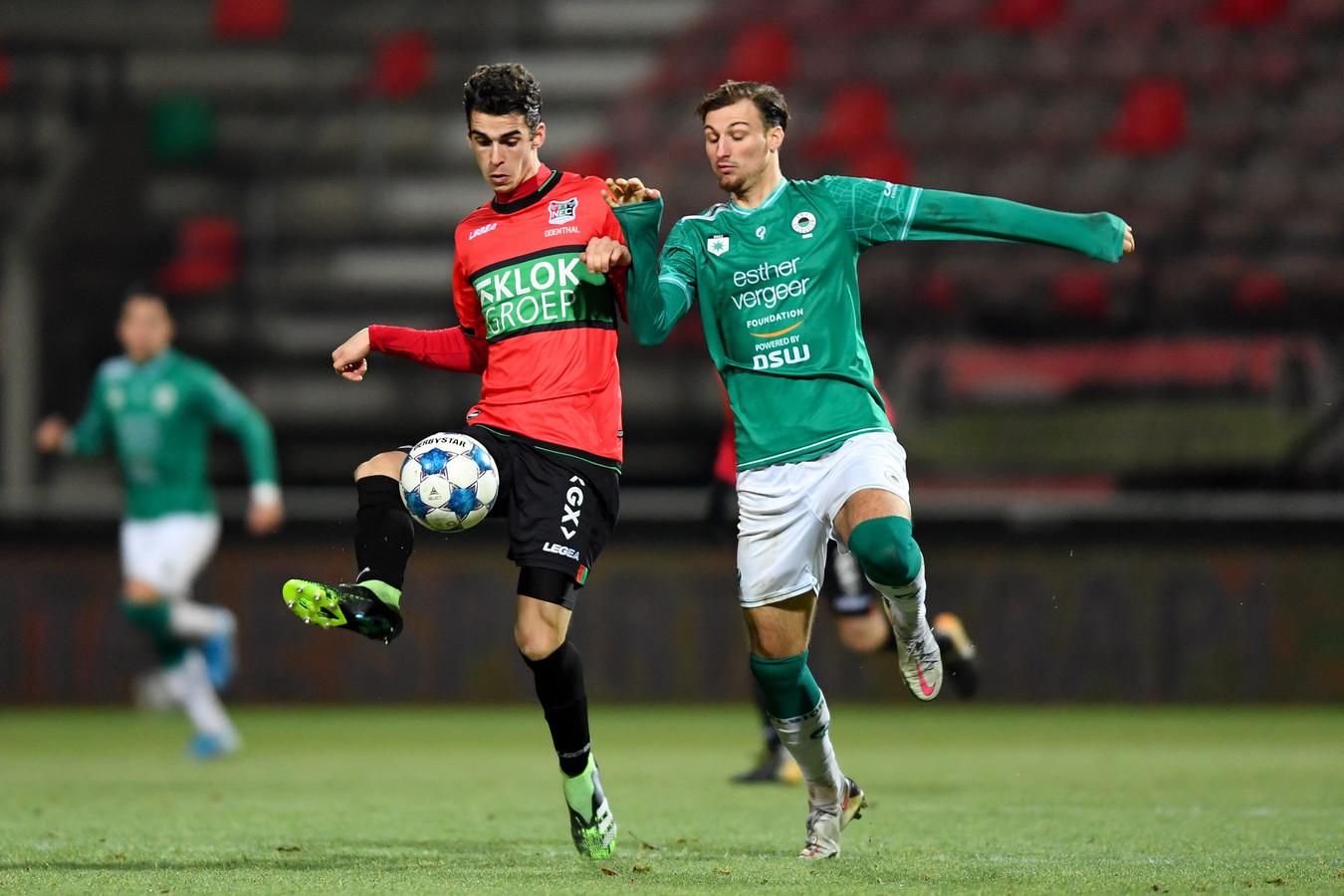 NEC'er Cas Odenthal heeft tegen Excelsior alleen oog voor de bal, rechts Stijn Meijer.